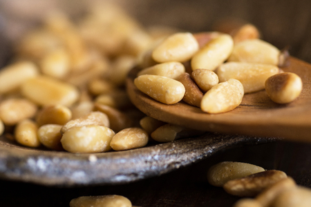 Pine Nuts on Dark Wooden Table. Toasted Organic Healthy Food. Stock Photo