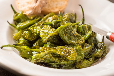 Grilled Padron Peppers in Rustic White Plate. Pimientos de Padron.