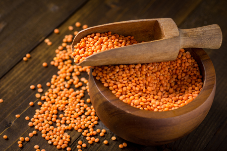 Healthy Organic Red Lentils in Bowl on Dark Wooden Table Foto de archivo