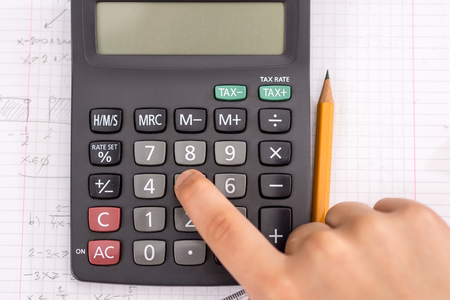 Finger on the Calculator Button During Mathematical Lesson. School Concept. Imagens
