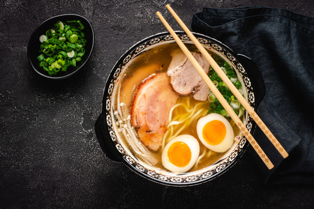 Japanese Ramen Soup with Udon Noodles, Pork, Eggs and Scallion on dark Stone Background 写真素材