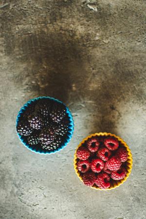 Blackberries and Raspberries in Ceramic Bowls on Rustic Stone Background