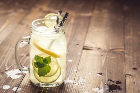 Cold Fresh Mojito Cocktail Lemonade with Ice, Lemon and Mint Leaves in Mason Jar on Rustic Dark Wooden Background. Summer Concept. 写真素材
