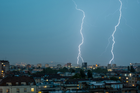 Lightning Thunderbolt Flash Strike Over City in the Night. Weather Concept.