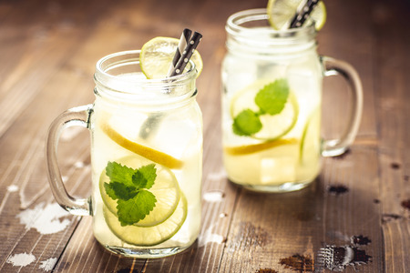 Cold Fresh Mojito Cocktail Lemonade with Ice, Lemon and Mint Leaves in Mason Jar on Rustic Dark Wooden Background. Summer Concept.
