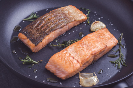 Grilled Salmon Fillets in Black Frying Pan with Rosemary and Garlic Reklamní fotografie