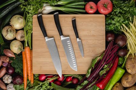 Küchenmesser-Set auf Holzschneidebrett mit frischem Gemüse. Vegane Rohkost. Gesundes Essen-Konzept. Standard-Bild