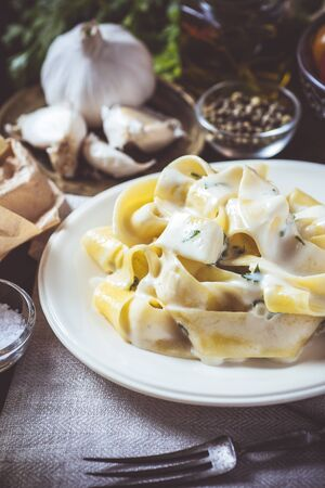 Old Recipe Traditional Italian Alfredo Pasta Plate with Creamy Cheese and Basil Sauce Stock fotó