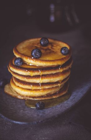 American Pancakes with Organic Berries and Maple Syrup on Dark Moody Background. Classic Homemade Breakfast.