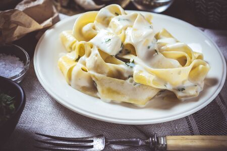 Old Recipe Traditional Italian Alfredo Pasta Plate with Creamy Cheese and Basil Sauce Banque d'images