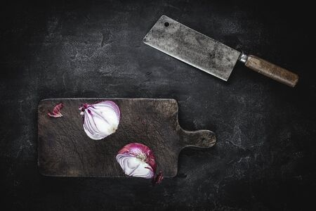 Fresh Halved Red Onion on Vintage Brown Cutting Board with Old Meat Cleaver