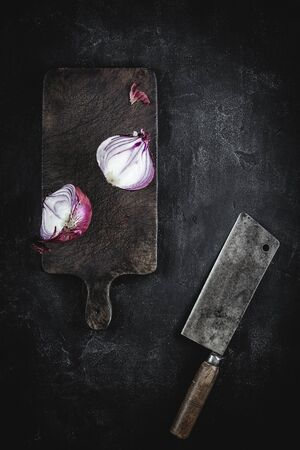 Fresh Halved Red Onion on Vintage Brown Cutting Board with Old Meat Cleaver Stock Photo