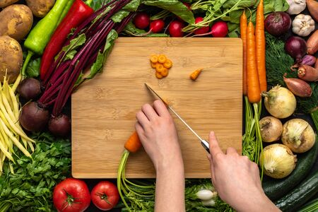 Female Hands Cutting Organic Carrot with Chef Knife on Wooden Chopping Board. Healthy Vegetarian Food Concept.