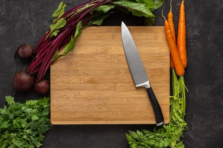 Chef Knife on Wooden Chopping Board with Fresh Vegetables Background. Healthy Eating Concept. Vegetarian Raw Food. Reklamní fotografie