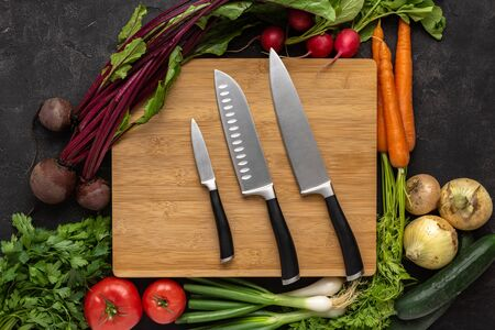 Kitchen Knives on Wooden Chopping Board with Fresh Vegetables Background. Healthy Eating Concept. Vegetarian Raw Food.