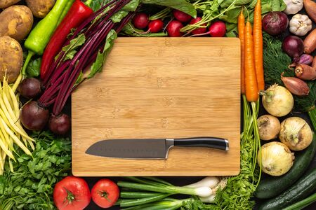 Santoku Knife on Wooden Cutting Board with Fresh Vegetables Background. Vegan Raw Food. Healthy Eating Concept.