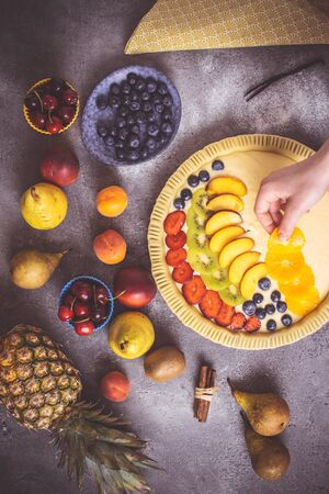 Female Hands Prepare Fruit Pie with Colorful Fruits and Fresh Dough. Healthy Food Concept. Reklamní fotografie