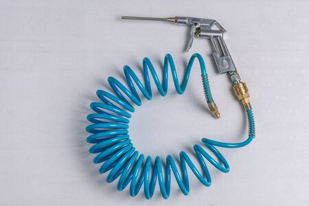 Air Compressor Blow Gun with Coiled Blue Hose on White Background
