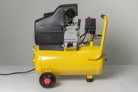 Compressore d'aria a pistone giallo. Macchina di compressione e fornitura di aria. Equipaggiamento tecnico. Archivio Fotografico