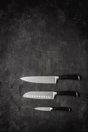 Modern Kitchen Knives Set on Dark Stone Background. Chef's Knives Concept.