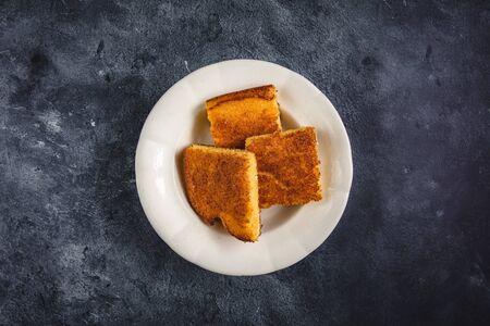 Corn Bread Squares Slices in White Plate on Dark Blue Rustic Background Reklamní fotografie