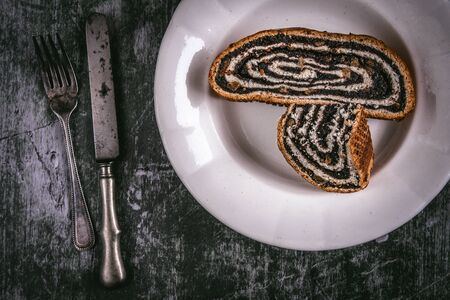 Poppy Seeds Strudel Roll Pie Slices on Rustic Plate and Green Background