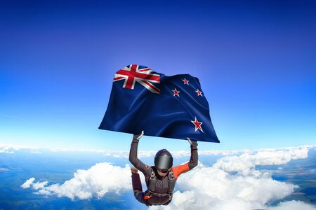 New Zealand extreme. Flag in skydiving. People in free fall grab flag of New Zealand. Patriotism, men and flag. Zdjęcie Seryjne