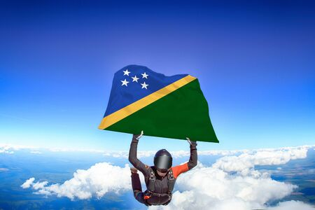 Solomon islands extreme. Flag in skydiving. People in free fall grab flag of Solomon islands. Patriotism, men and flag.