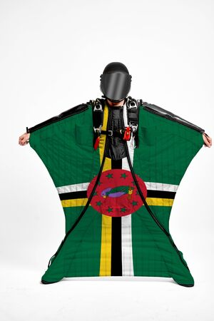 Dominica extreme. Flag in skydiving. People in free fall grab flag of Dominica. Patriotism, men and flag.
