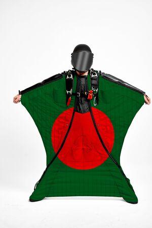 Bangladesh extreme. Flag in skydiving. People in free fall grab flag of Bangladesh. Patriotism, men and flag.