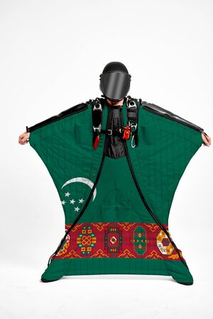 Turkmenistan extreme. Flag in skydiving. People in free fall grab flag of Turkmenistan. Patriotism, men and flag.