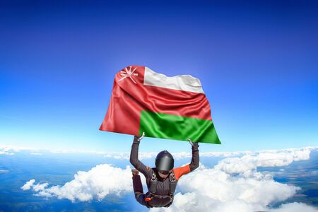 Oman extreme. Flag in skydiving. People in free fall grab flag of Oman. Patriotism, men and flag.
