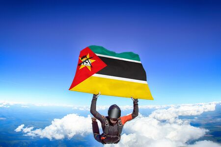 Mozambique extreme. Flag in skydiving. People in free fall grab flag of Mozambique. Patriotism, men and flag. 스톡 콘텐츠