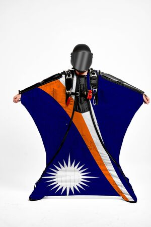 Marshall Islands extreme. Flag in skydiving. People in free fall grab flag of Marshall Islands. Patriotism, men and flag. 스톡 콘텐츠