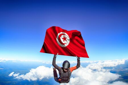 Tunisia extreme. Flag in skydiving. People in free fall grab flag of Tunisia. Patriotism, men and flag. 스톡 콘텐츠