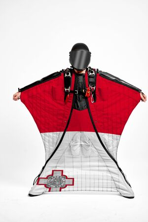 Malta extreme. Flag in skydiving. People in free fall grab flag of Malta. Patriotism, men and flag.