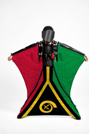 Vanuatu extreme. Flag in skydiving. People in free fall grab flag of Vanuatu. Patriotism, men and flag. 스톡 콘텐츠