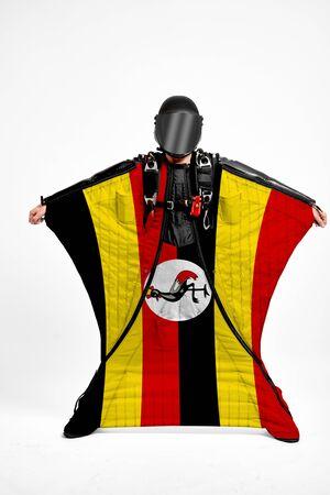 Uganda extreme. Flag in skydiving. People in free fall grab flag of Uganda. Patriotism, men and flag. 스톡 콘텐츠
