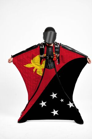 Papua New Guinea extreme. Flag in skydiving. People in free fall grab flag of Papua New Guinea. Patriotism, men and flag. 스톡 콘텐츠