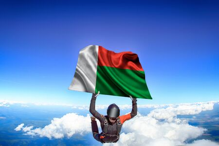 Madagascar extreme. Flag in skydiving. People in free fall grab flag of Madagascar. Patriotism, men and flag.