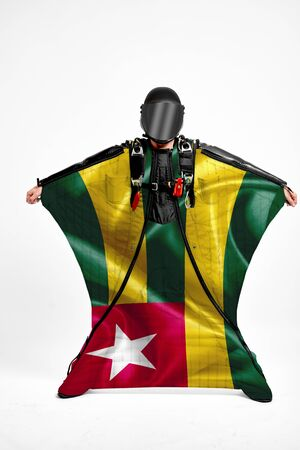Togo extreme. Flag in skydiving. People in free fall grab flag of Togo. Patriotism, men and flag. 스톡 콘텐츠