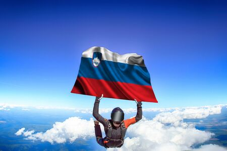 Slovakia extreme. Flag in skydiving. People in free fall grab flag of Slovakia. Patriotism, men and flag. 스톡 콘텐츠