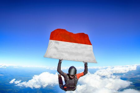 Indonesia extreme. Flag in skydiving. People in free fall grab flag of Indonesia. Patriotism, men and flag.