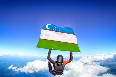 Uzbekistan extreme. Flag in skydiving. People in free fall grab flag of Uzbekistan. Patriotism, men and flag.