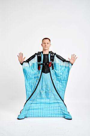 Ten fingers. Men in wing suit show ten fingers. Skydiving men in parashute. Simulator of free fall. Stock fotó