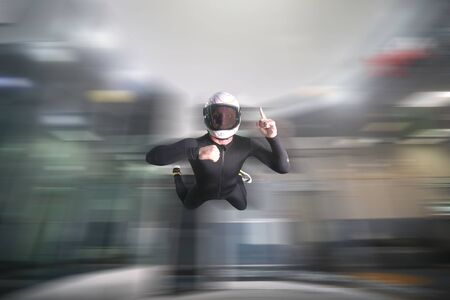 One finger. Fly men show one finger. Sky diver in black suit. Teampleat skydiver. Stock Photo