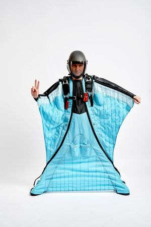Two fingers. Men in wing suit show two fingers. Skydiving men in parashute. Simulator of free fall.