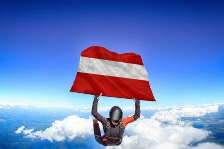 Austria extreme. Flag in skydiving. People in free fall grab flag of Austria. Patriotism, men and flag.