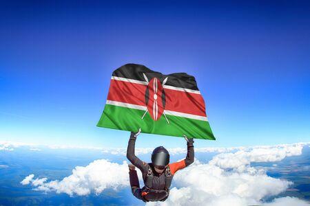 Kenya extreme. Flag in skydiving. People in free fall grab flag of Kenya. Patriotism, men and flag. Фото со стока
