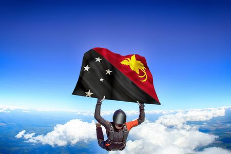 Papua New Guinea extreme. Flag in skydiving. People in free fall grab flag of Papua New Guinea. Patriotism, men and flag. Фото со стока